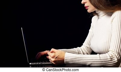 Beautiful brunette woman making online payment with her credit card using laptop. Black background, warm colors, space for inscriptions or infographics. Ecommerce concept.