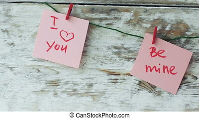 Valentine's cards with red clips on rustic wood background,
