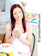 Pensive woman eating her breakfast at home holding a cup