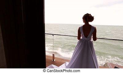 Bride posing at balcony at sea resort hotel