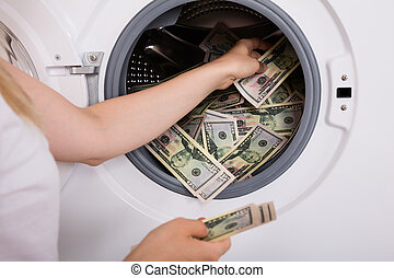 Person Inserting Money In Washing Machine - Close-up Of...