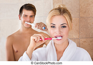 Portrait Of Man And Woman Brushing Teeth