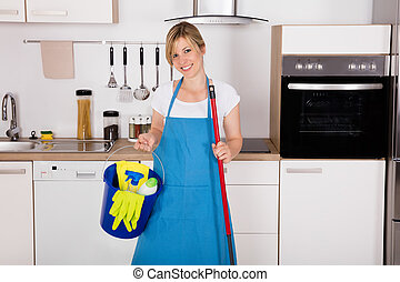 Housemaid Holding Cleaning Equipment In Kitchen - Cleaning...