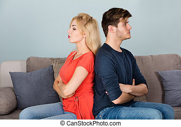 Unhappy Couple With Arms Crossed Sitting On Sofa