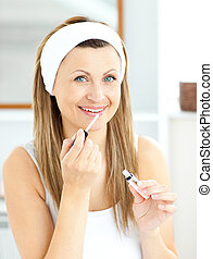 Bright woman applying gloss on her lips in the bathroom