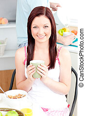 Charming woman eating her breakfast at home
