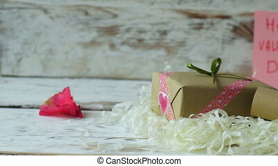 Red rose petals falling down on wooden table.