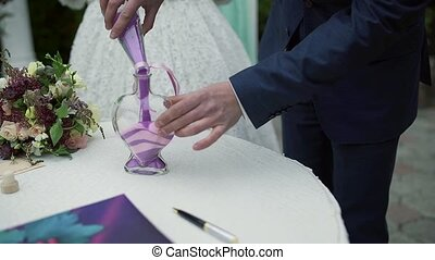 A wedding ceremony with a mixed family. The groom, mother, and son perform a unity sand ceremony mixing each of their colors into one beautiful piece of art.