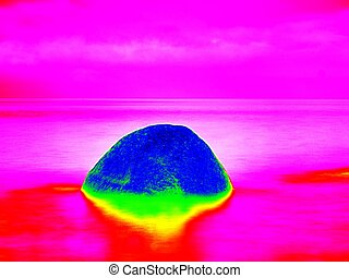 Infrared photo.. Boulders at island shore stick up from...