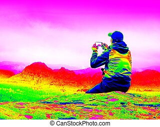 Infrared photo. Man in sportswear on cliff edge -...