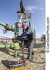 Oilfield worker - Worker reparing wellhead with the wrench...