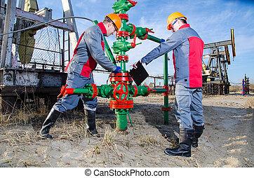 Oilfield workers - Workers in the oilfield, one repairing...