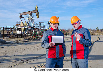 Workers in the oilfield talking on the radio