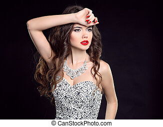Portrait of a sexy brunette girl model with red lips and long wavy hairstyle posing isolated on black studio background.
