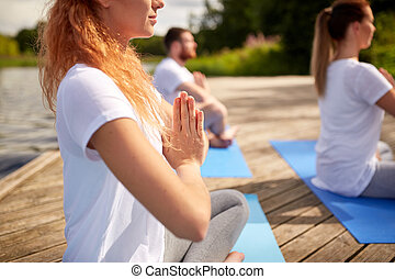 close up of people making yoga exercises outdoors - fitness,...