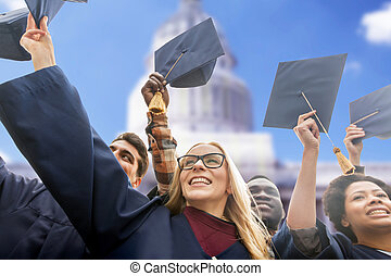 happy students or bachelors waving mortar boards -...