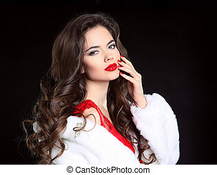 Beautiful Fashion brunette Girl portrait in white Mink Fur Coat. Red lips makeup. Beauty Luxury winter woman with long curly hair style posing isolated on studio black background.