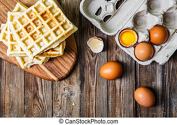 Several Belgian waffles with eggs on wooden table