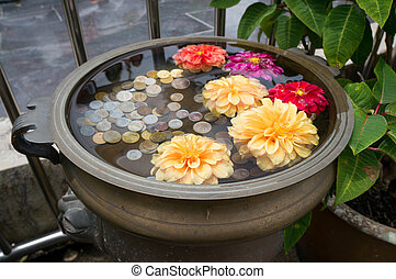 A small floral wishing well with coins on Penang Hill,...