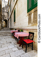narrow European street with tables and chairs from a restaurant in the historic center of Sibenik, Croatia