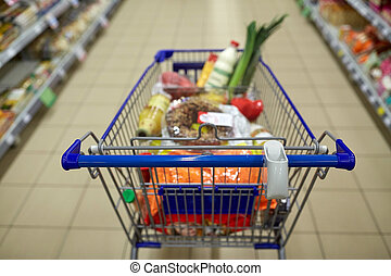 food in shopping cart or trolley at supermarket