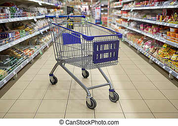 empty shopping cart or trolley at supermarket - consumerism...