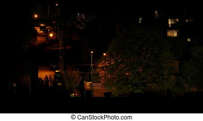 Car Drives Up Hill Next To Apartments At Night - Car turns...