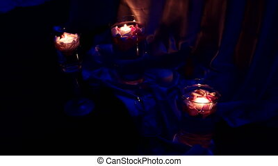 Element of the decor - burning candles in candleholders with rose petals.