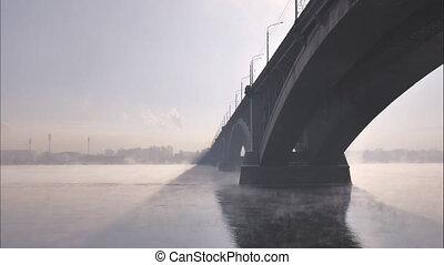 winter cityscape, the automobile bridge in the backlight,...