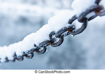 old rusty iron chain on a frost covered with snow - rusty...