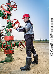 Worker near wellhead - Oilfield worker repairing well head...