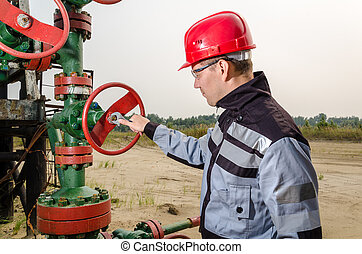 Worker near wellhead - Oilfield worker repairing wellhead...