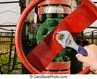 Wellhead valve repair with the wrench. Oil and gas concept.