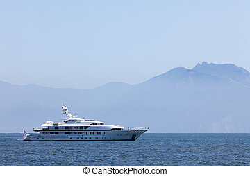 Cruising yacht in the sea on the background of mountains -...