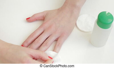 Women remove nail polish on white table