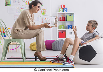 Boy during session with psychologist - Boy sitting on modern...