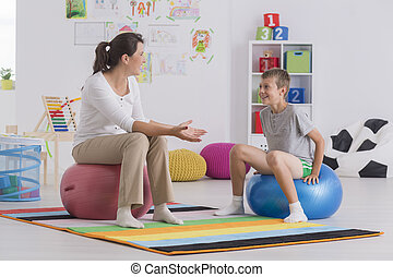 Physiotherapist sitting on gym ball - Young physiotherapist...