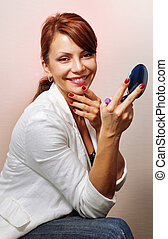 happy woman with blue compact mirror - beautiful woman...
