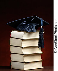 Knowledge - graduation cap on top of the stack of books, for...