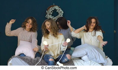 Four beautiful girls dance, shake heads and hair on bed celebrate party slowmotion