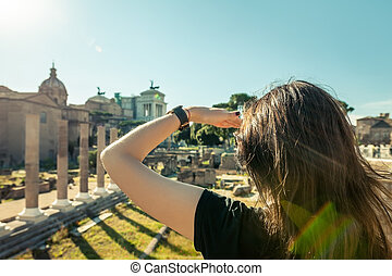 Woman looking forward with hand on forehead to archeological...