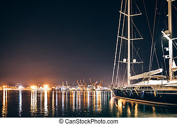 Luxury yacht in La Spezia at night with reflection in water...