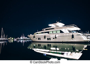Luxury yachts in La Spezia harbor at night with reflection...