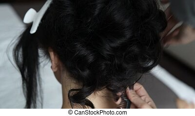 Hairdresser is finishing hairstyle for bride indoor