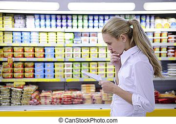 woman reading her shopping list in the supermarket with copy...