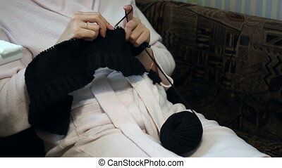 A woman in a housecoat engaged in knitting. Hands shot up close. The product is made of black thread. Work knitting needles.