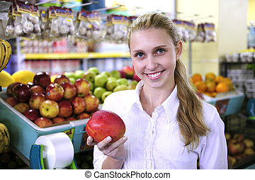 Woman shopping for fruits in the supermarket holding a mango
