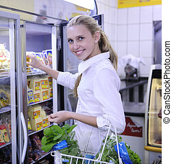 Woman shopping for frozen food in the supermarket - Blond...