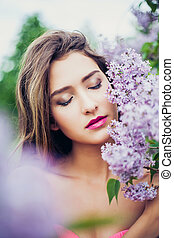 Portrait of young beautiful woman posing among lilac. Closed...