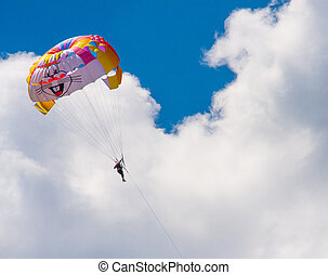 tourist attraction parasailing on cloudy sky background.